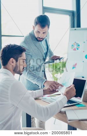 Look at this! Two male partners are discussing the data in report sharing opinions and ideas in light modern work station wearing smart clothes