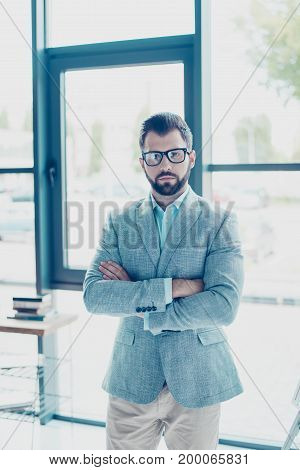 Young successful bearded nerdy man is standing in his office in formal suit and glasses with crossed hands looking serious severe harsh and strict. Behind him is a workplace and windows