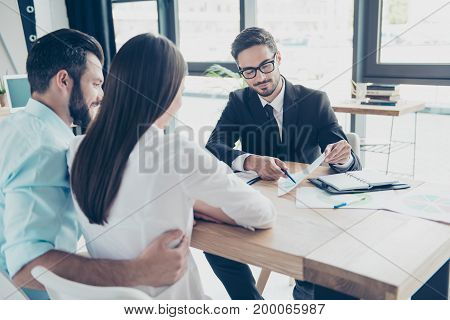 Rear Shot Of Young Family, Making A Deal With Lawyer About Their Business. Men Is Showing The Persen