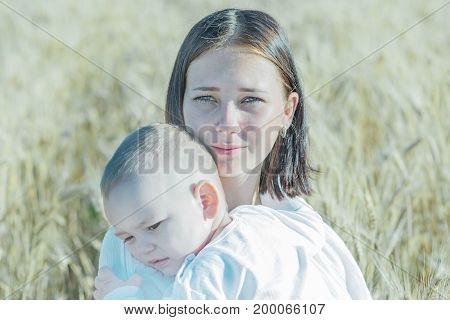 Portrait of a pretty young calm mother holding a small sleepy child in wheat field at sunny summer day