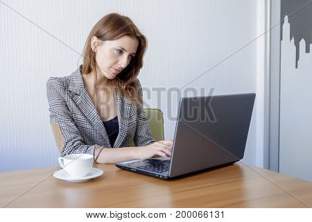 Cute young female adult working on laptop computer at desk next to coffee cup in office