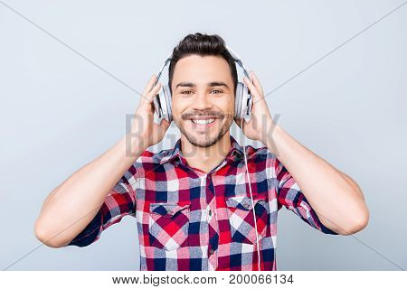 Happy Young Cute Guy Is Listening To The Music In Big White Headphones On Light Blue Backgroung, Hol