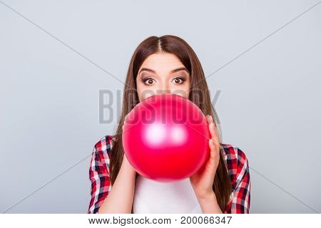 Young Amazed Brown-haired Girl Is Blowing Red Balloon For Birthday Party And Looking At The Camera O