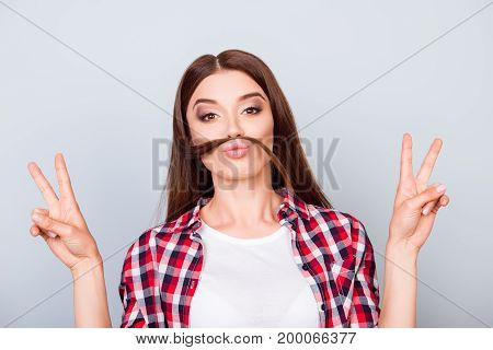 Go Crazy! Playful Funny Brown-haired Girl Is Making A Mustache Of Her Hair And Shows Peace Signs, In