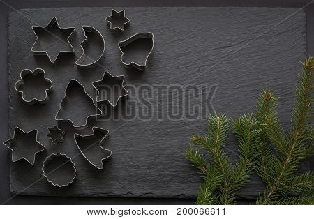 Various Christmas-themed cookie cutters. Christmas cookie cutters on black. Holiday card.