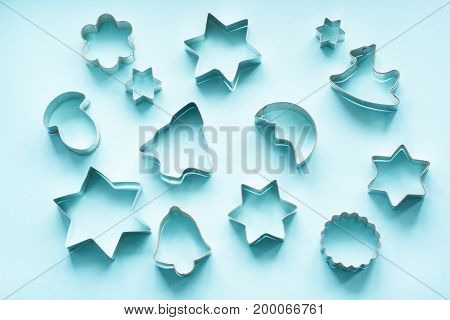 Various Christmas-themed cookie cutters.Christmas cookie cutters on blue. Holiday card.