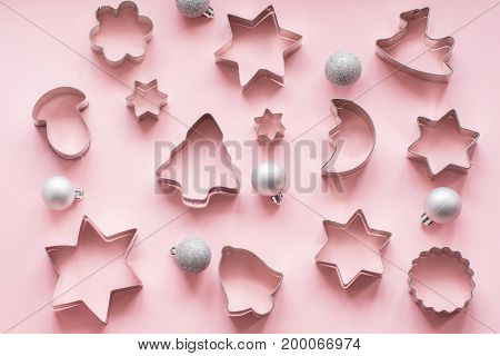 Various Christmas-themed cookie cutters on pink. Holiday card. View from above. Flat lay.