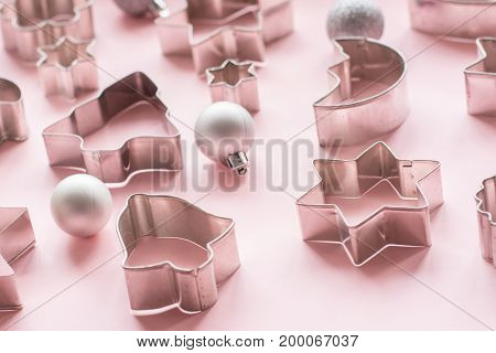 Various Christmas-themed cookie cutters on pink. Holiday card. Pattern.