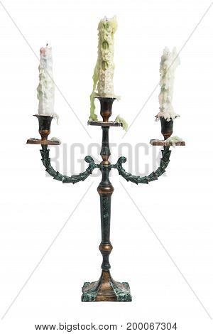 Old vintage ancient baroque used dirty metal shiny candlestick with three candle holders with old white and green melted candles on isolated white background.