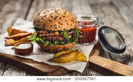 BBQ hamburgers on cutting board with tomato sauce and french fries