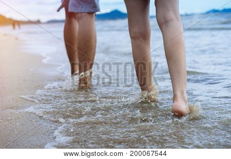 Close up lower body man and girl couple walking at beach in sunlight