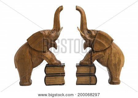 Two vintage old wooden carved brown elephants holders with raised trunks and opened mouth standing on books with front legs on isolated white background.