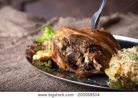 Tasty roast pork knuckle with fried potato and sauerkraut