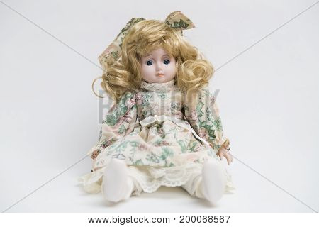 Portrait of ceramic porcelain handmade vintage doll with curly blond hair in old white textile dress with gentle floral pink, green, beige print and embroidery, bow, white boots on white background.