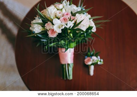 Beautiful Bouquet Of Flowers Of The Bride And Boutonniere Lie On The Table