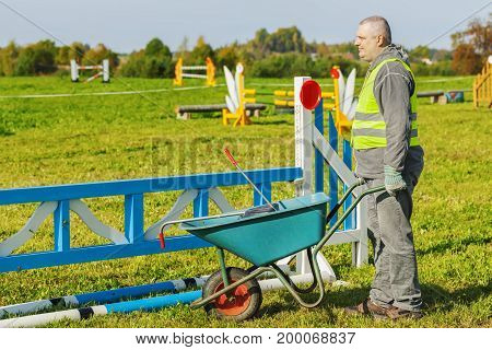 Horse handler with wheelbarrow on hurdle field