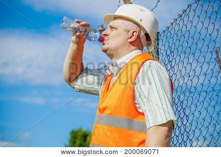 Engineer with bottle of water in summer day