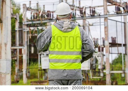 Electrician talking on the phone in electrical substation