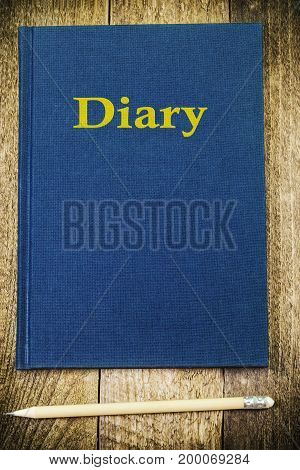 Diary with pencil on wood in backgrounds