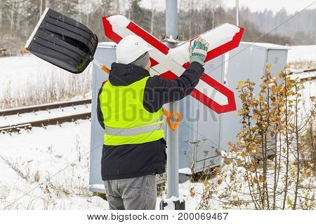 Railroad employee clean snow from the warning sign near railway crossing