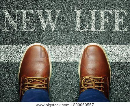 Man near inscription new life on asphalt