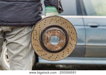 Man holding old brake disc near car