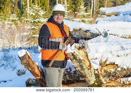 Lumberjack with ax near pile of logs in winter