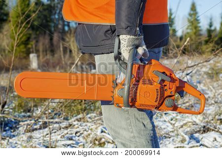 Lumberjack with chainsaw in winter day .