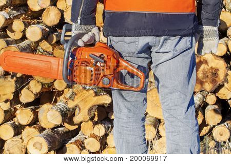 Lumberjack with chainsaw near logs in winter day