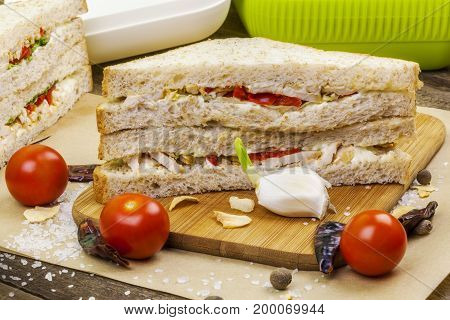 Sandwiches on wooden table in room .