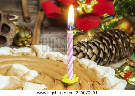 Burning candle in chocolate cake near Christmas decoration