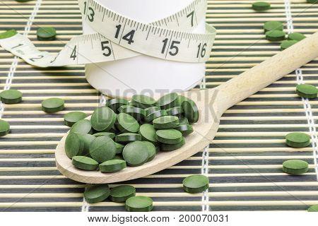Spirulina,chlorella pills on wood spoon and measure tape