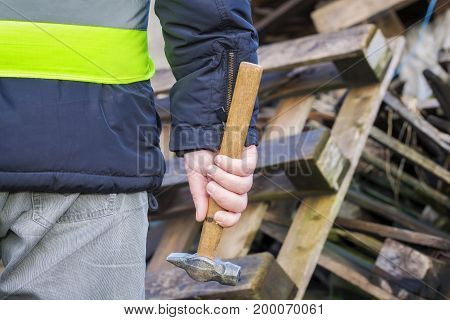 Worker with hammer near wooden pallets .
