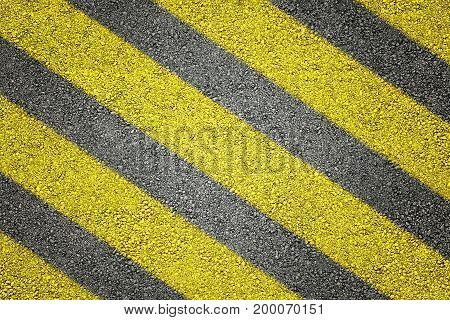 Yellow stripes on asphalt in backgrounds .
