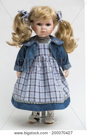 Portrait of ceramic porcelain handmade vintage doll with wavy blond hair with tails in old blue plaid textile dress, denim jacket with embroidery, bow, striped sweater, sneakers on white background.
