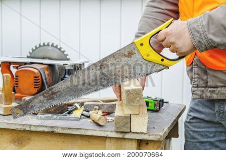 Carpenter sawing timber in autumn day .