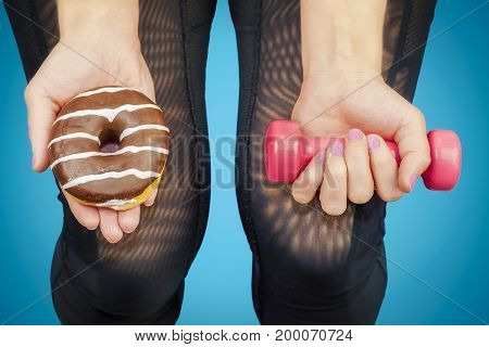 Woman with dumbbell and donut in the hands of
