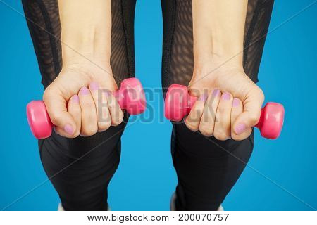 Woman with two dumbbells on legs .