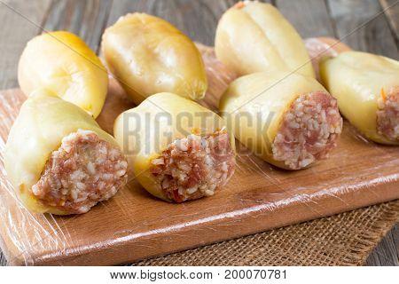 Raw peppers stuffed with meat and rice on a cutting board