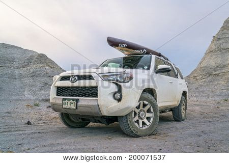 Castle Rock, KS, USA - August 14, 2017:  Toyota 4Runner SUV (2016 Trail edition) carrying  a stand up paddleboard  is driving through badlands and prairie of Kansas.