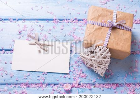 Wrapped box with present empty tag and decorative white heart on blue wooden planks. Selective focus. Place for text.