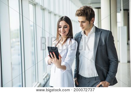 Cheerful Business Woman And Man Working Together On Tablet In Office Hall