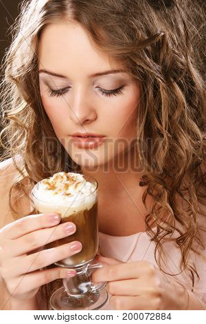 Portrait of young blond happy woman holding cafe latte cup
