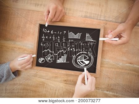 Digital composite of Hands writing equations on blackboard