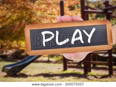 Digital composite of play text on blackboard in front of playground