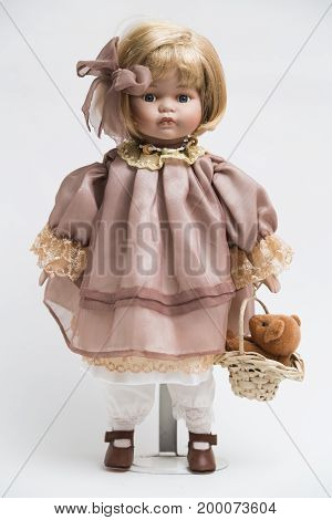 Portrait of ceramic porcelain handmade vintage doll with blond hair in old linen pink dress with golden yellow embroidery, in pants, bow, red shoes, wicker basket with teddy bear on white background.