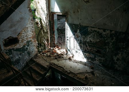 Interior of dark ruined abandoned building, door in sunlight, broken staircase, toned