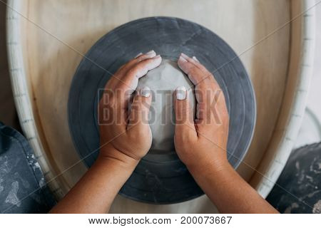 Hands of woman potter, ready to work with white clay at pottery wheel, top view, selective focus