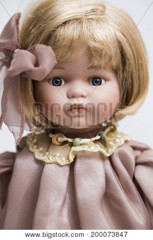 Portrait of ceramic porcelain handmade vintage doll with necklace, blond hair in old linen pink dress with golden yellow embroidery, bow on white background.