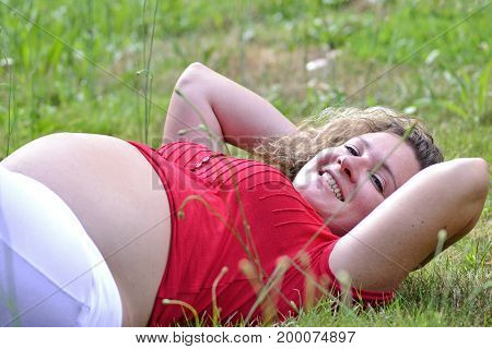 lying down pregnant woman on grass garden.